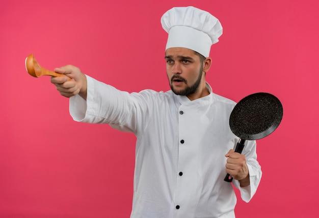 シェフの制服を着た印象的な若い男性料理人が、フライパンを持ち、スプーンを伸ばし、ピンクの壁に隔離された側を見る