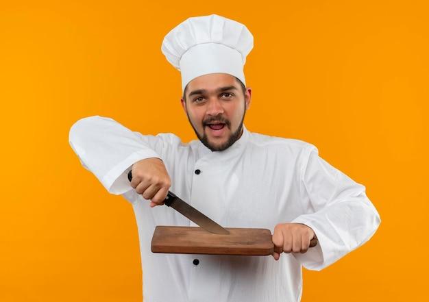오렌지 벽에 고립 된 칼과 커팅 보드를 들고 요리사 유니폼에 감동 된 젊은 남성 요리사