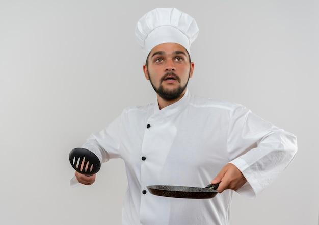 Впечатленный молодой мужчина-повар в униформе шеф-повара держит шумовку и сковороду, глядя вверх изолированно на белой стене