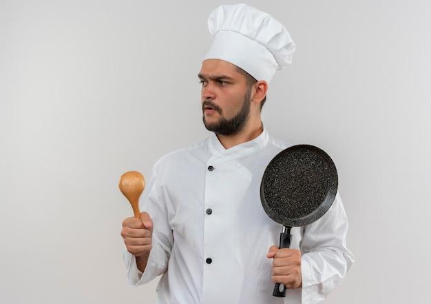 コピー スペースで白い壁に分離されたスプーンとフライパンを保持しているシェフの制服を着た印象的な若い男性料理人