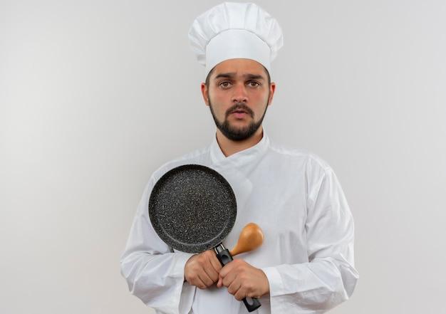 복사 공간이 흰 벽에 고립 된 숟가락과 프라이팬을 들고 요리사 유니폼에 감동 된 젊은 남성 요리사