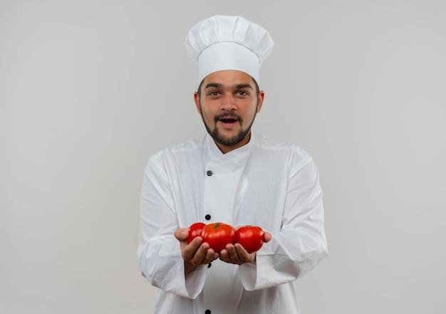 Впечатленный молодой мужчина-повар в униформе шеф-повара держит помидоры на белой стене с копией пространства