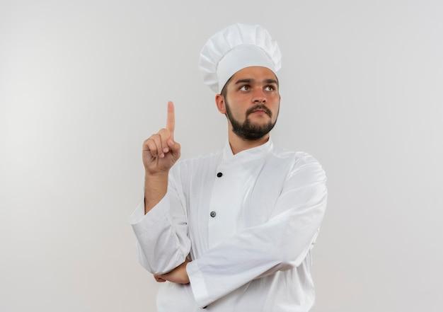 側を見て、コピー スペースで白い壁に分離された指を上げるシェフの制服を着た感銘を受けた若い男性料理人