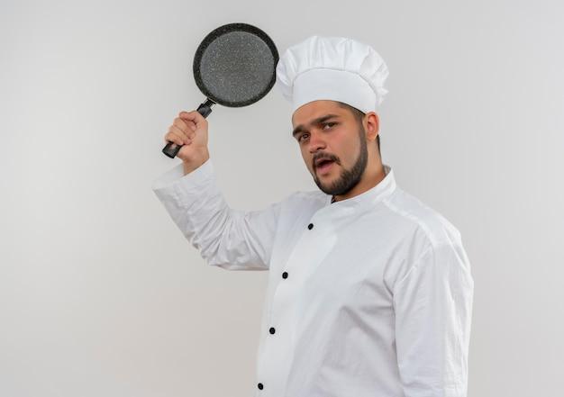 コピー スペースで白い壁に分離されたフライパンを上げるシェフの制服を着た感銘を受けた若い男性料理人