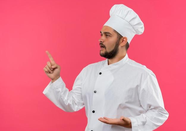 コピー スペースを持つピンクの壁に分離された側を見て、指している空の手を示すシェフの制服を着た感銘を受けた若い男性料理人