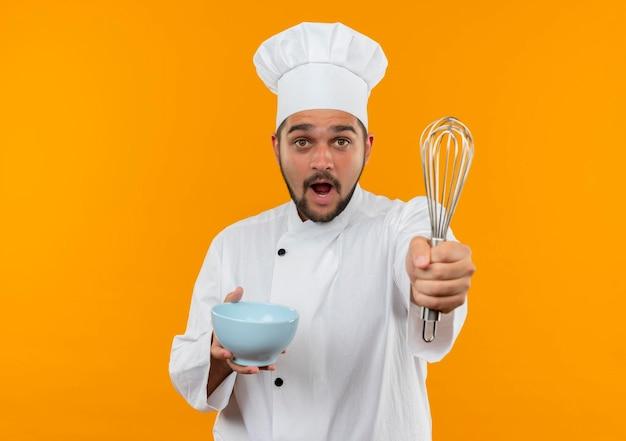 シェフの制服を着た印象的な若い男性料理人が泡立て器を伸ばし、オレンジ色の壁にコピースペースで隔離されたボウルを保持