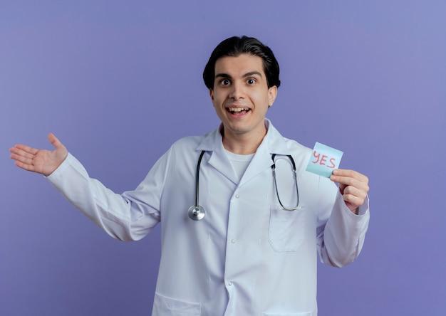 Впечатленный молодой мужчина-врач в медицинском халате и стетоскопе показывает примечание да и пустую руку, изолированную на фиолетовой стене