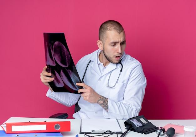Впечатленный молодой мужчина-врач в медицинском халате и стетоскопе сидит за столом с рабочими инструментами, держит рентгеновский снимок и смотрит на стол, изолированный на розовом