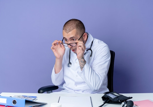 의료 가운과 청진기를 착용하고 안경을 착용하고 보라색에 고립 된 폴더를보고 작업 도구로 책상에 앉아 감동 된 젊은 남성 의사