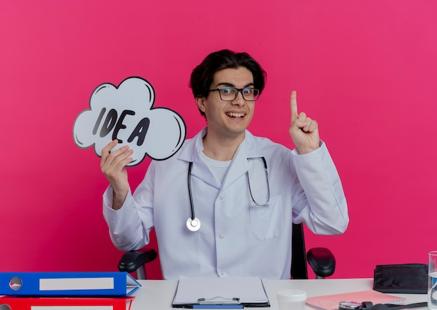 핑크 벽에 고립 된 아이디어 거품 제기 손가락을 들고 의료 도구와 책상에 앉아 안경 의료 가운과 청진기를 입고 감동 된 젊은 남성 의사
