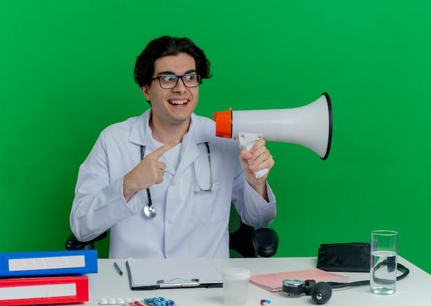 Впечатленный молодой мужчина-врач в медицинском халате и стетоскоп в очках, сидя за столом с медицинскими инструментами, держа спикера, глядя и указывая на сторону, изолированную на зеленой стене