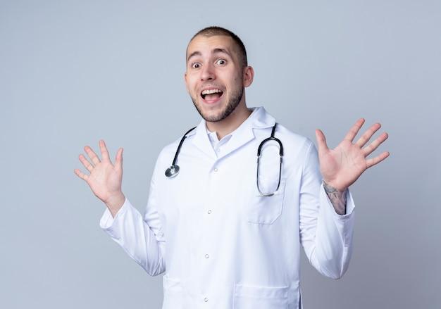 Giovane medico maschio impressionato che indossa veste medica e stetoscopio intorno al collo che mostra le mani vuote isolate su bianco