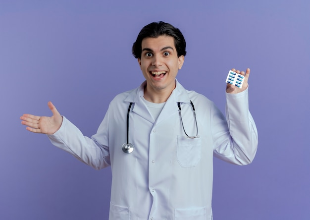 Impressionato giovane medico maschio che indossa veste medica e stetoscopio che mostra il pacchetto di capsule che mostra la mano vuota isolata sulla parete viola