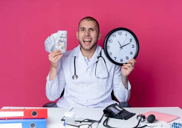 Impressionato giovane medico maschio che indossa abito medico e stetoscopio seduto alla scrivania con strumenti di lavoro in possesso di denaro e orologio isolato sul rosa