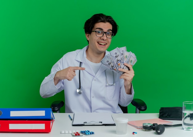 Impressed young male doctor wearing medical robe and stethoscope with glasses sitting at desk with medical tools  holding and pointing at money isolated on green wall