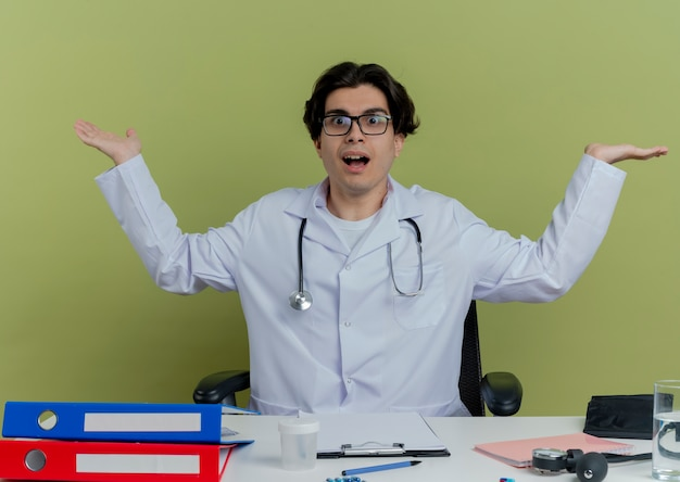 Giovane medico maschio impressionato che porta veste medica e stetoscopio con gli occhiali che si siedono allo scrittorio con gli strumenti medici che osservano che mostrano le mani vuote isolate