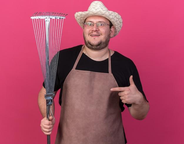 핑크 벽에 고립 된 잎 갈퀴에서 원예 모자 지주와 포인트를 입고 감동 젊은 남성 정원사