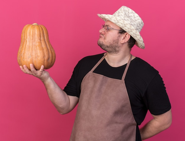 Impressed young male gardener wearing gardening hat holding and looking pumpkin isolated on pink wall