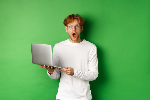 안경에 인상적인 젊은 남자가 턱을 떨어 뜨리고 녹색 배경 위에 서있는 노트북에서 프로모션을 읽은 후 놀랐습니다.