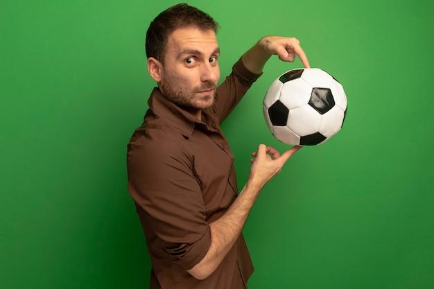Giovane impressionato che sta nella vista di profilo che tiene il pallone da calcio che esamina la parte anteriore isolata sulla parete verde