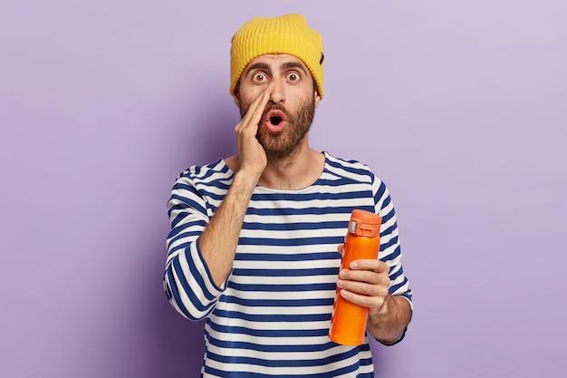 Il giovane colpito sussurra pettegolezzi a qualcuno con un'espressione omg, tiene la bocca aperta, tiene la fiaschetta con la bevanda, indossa un cappello giallo e un maglione da marinaio prova sorpresa e incredulità. che terribile notizia!