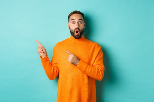 Impressed young man with beard, reacting to promo banner, pointing fingers left, showing logo and looking surprised, standing over turquoise background.