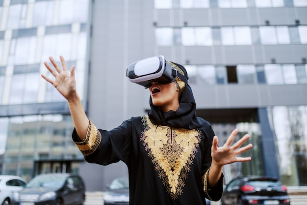 Impressed young muslim woman in traditional wear standing outdoors, using vr goggles and trying to touch what she sees.