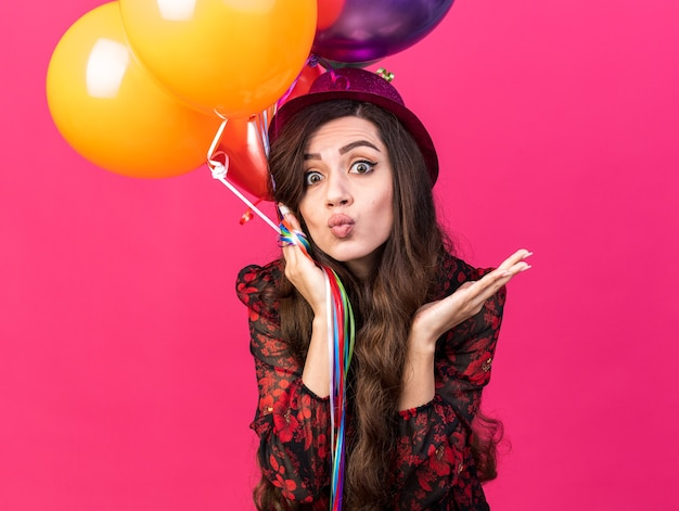Impressed young party girl wearing party hat holding balloons  doing kiss gesture showing empty hand isolated on pink wall