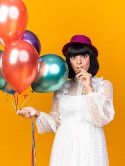 オレンジ色の壁に分離された口の中でパーティーホーンを保持している風船を保持しているパーティー帽子をかぶっている感動の若いパーティーの女の子