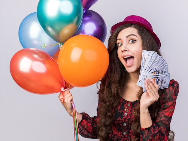 Impressed young party girl wearing party hat holding balloons and money looking at camera isolated on white wall