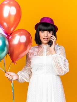 Impressed young party girl wearing party hat holding balloons talking on phone  isolated on orange wall