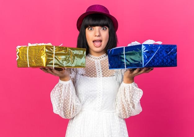 분홍색 벽에 격리된 선물 꾸러미를 들고 파티 모자를 쓴 젊은 파티 소녀