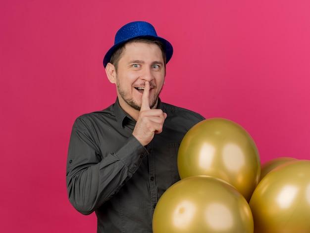 ピンクで隔離の沈黙のジェスチャーを示す風船を保持している青い帽子をかぶっている感動の若いパーティーの男