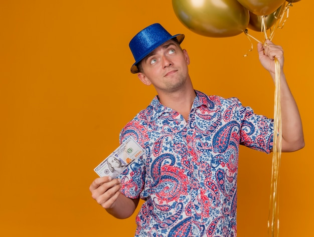 Impressed young party guy wearing blue hat holding balloons with cash isolated on orange
