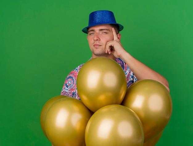 Ragazzo giovane partito impressionato che indossa cappello blu in piedi dietro palloncini e mettendo la mano sul tempio isolato sul verde