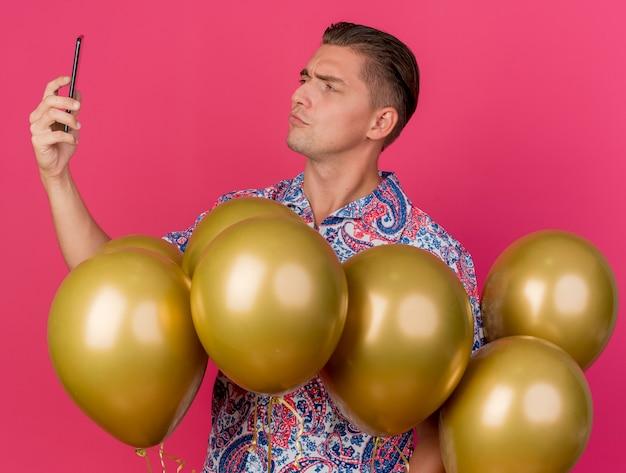 風船の間に立っているカラフルなシャツを着て、ピンクで隔離された自分撮りを撮る感動の若いパーティー男