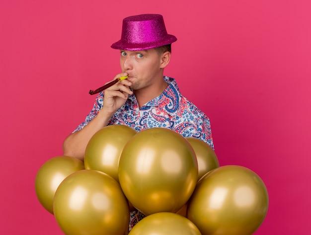 Впечатленный молодой тусовщик в розовой шляпе, стоящий за воздушными шарами и дует вентилятор, изолированный на розовом