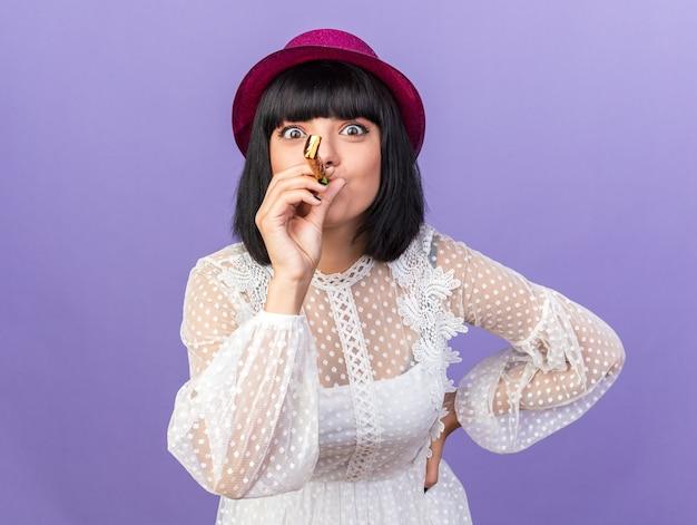 紫色の壁で隔離された正面を見て腰に手を保ちながらパーティーハットを吹くパーティーホーンを身に着けている感動の若いパーティーの女性