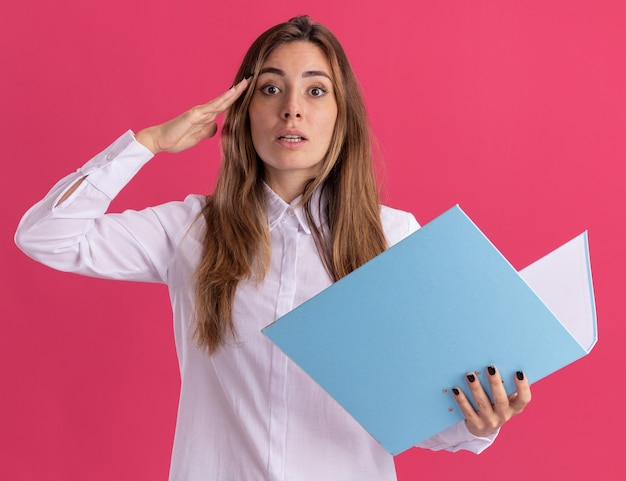 Impressed young pretty caucasian girl doing salute gesture and holds file folder on pink
