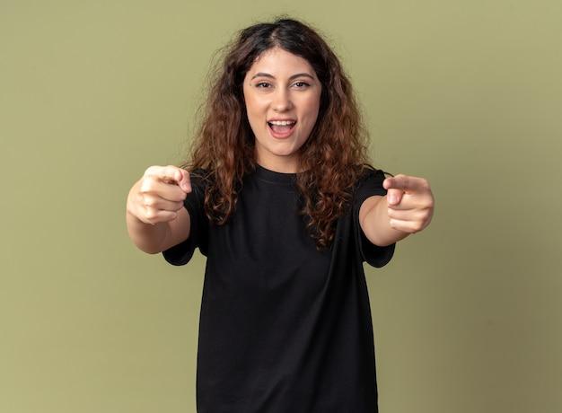Impressionata giovane bella ragazza caucasica che ti fa un gesto isolato sulla parete verde oliva con spazio per le copie
