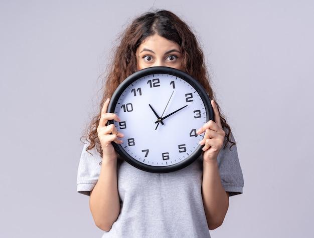 복사 공간이 있는 흰색 벽에 격리된 뒤에서 시계를 들고 있는 젊은 백인 소녀