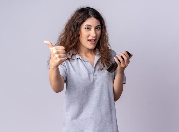 Впечатленная молодая симпатичная кавказская девушка, держащая мобильный телефон, показывает палец вверх
