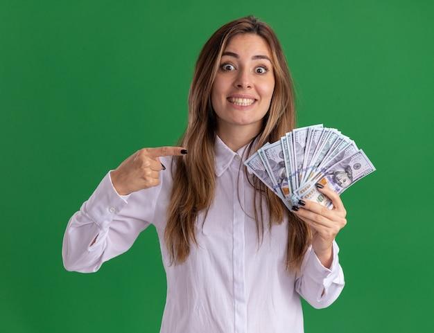 La giovane ragazza abbastanza caucasica impressionata tiene e indica i soldi isolati sulla parete verde con lo spazio della copia