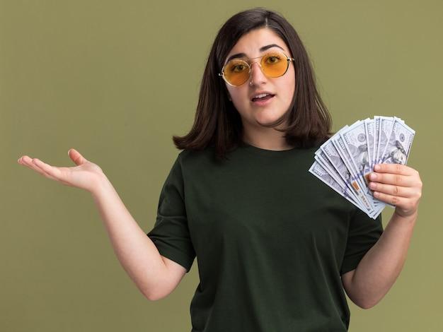 Впечатленная молодая симпатичная кавказская девушка в солнцезащитных очках держит деньги и держит руку открытой на оливково-зеленом Бесплатные Фотографии