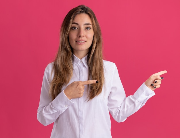 Impressed young pretty caucasian girl points at side with two hands isolated on pink wall with copy space