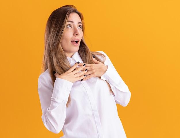 感動した若いかなり白人の女の子は胸に手を置き、コピースペースでオレンジ色の壁に隔離された側を見ます