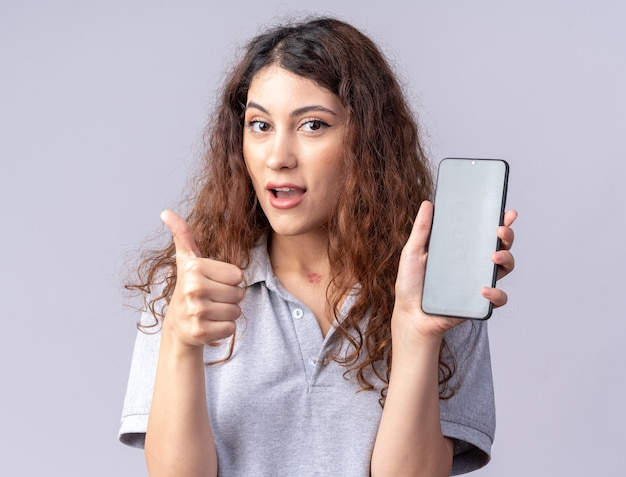 Впечатленная молодая симпатичная кавказская девушка показывает мобильный телефон и показывает палец вверх
