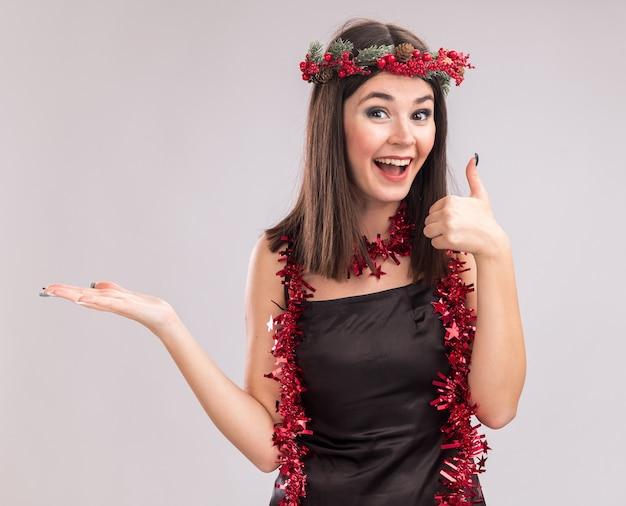 クリスマスの頭の花輪と首の周りに見掛け倒しの花輪を身に着けている感動の若いかなり白人の女の子は、白い背景で隔離のカメラを見て空の手と親指を示しています