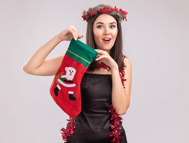 Impressed young pretty caucasian girl wearing christmas head wreath and tinsel garland around neck holding christmas stocking looking at camera isolated on white background with copy space