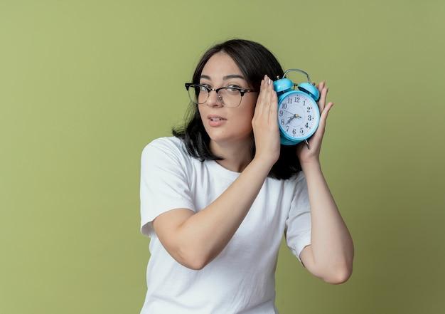 Впечатленная молодая симпатичная кавказская девушка в очках держит будильник на оливково-зеленом фоне с копией пространства